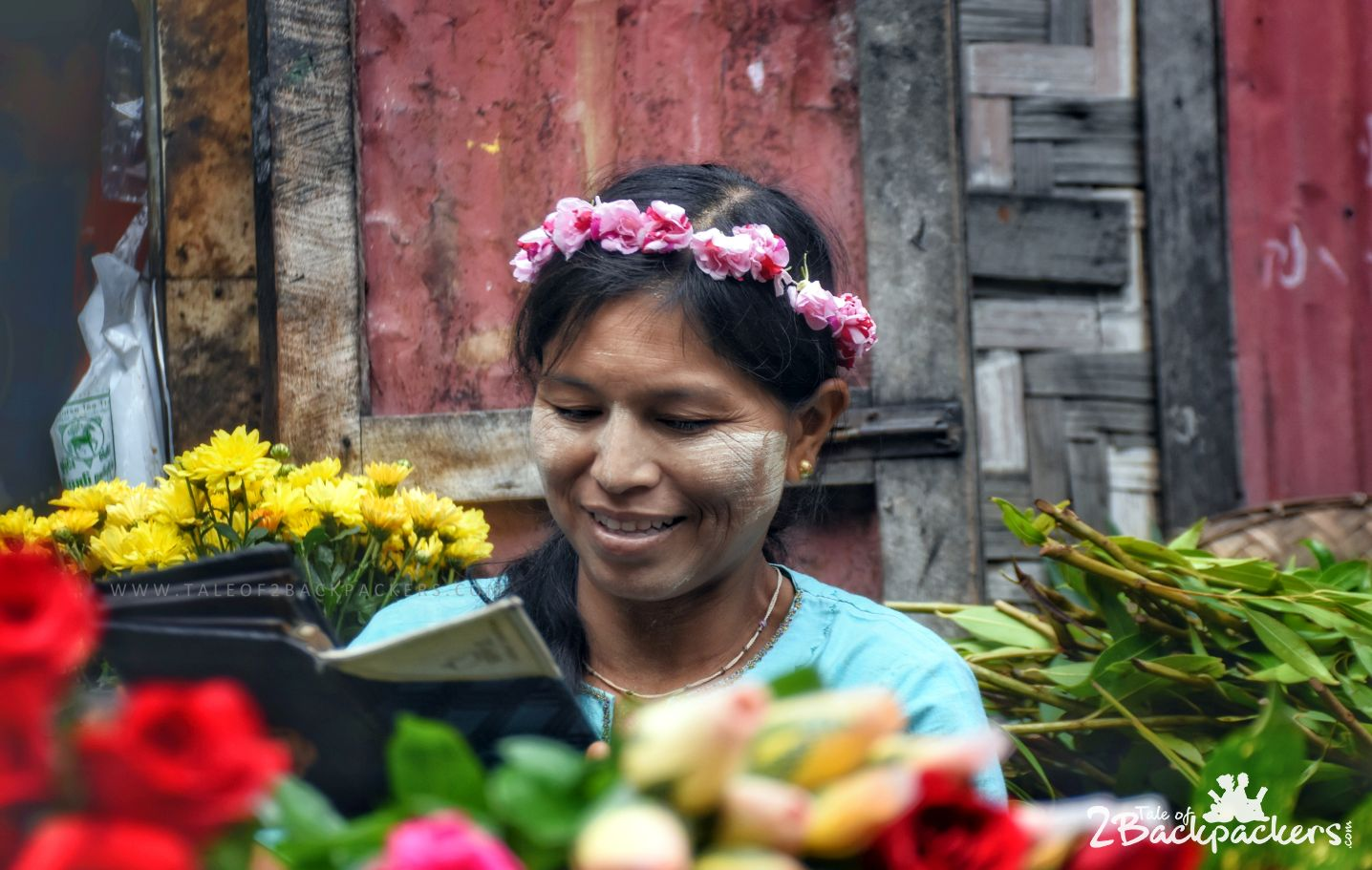 A girl smiling at Myanmar market - know more about our Myanmar backpacking trip