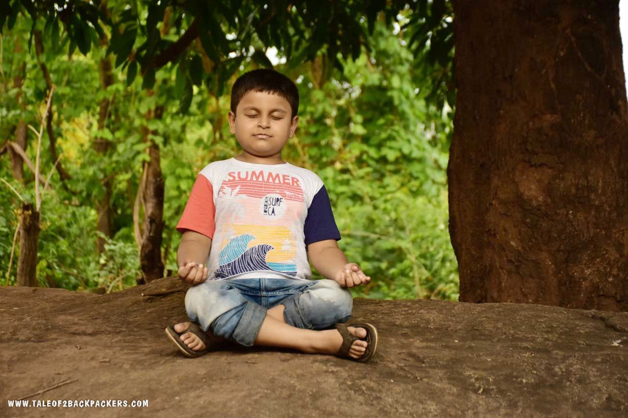Small boy meditating under a tree at Lovers point, Daringbadi