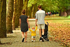 Parents and kid walking in park with a stroller