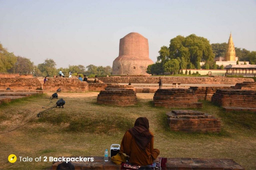 A monk praying at Sarnath Buddhist Complex in front of Dhamekh Stupa