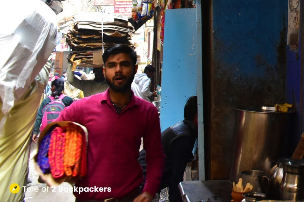 A person carrying sarees - in alleys of Varanasi
