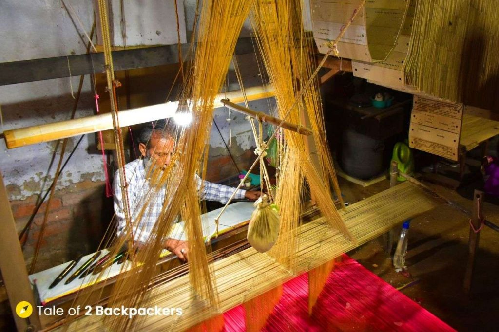 A weaver or bunkaar working at the loom. jacquard looms are used for designing the brocades