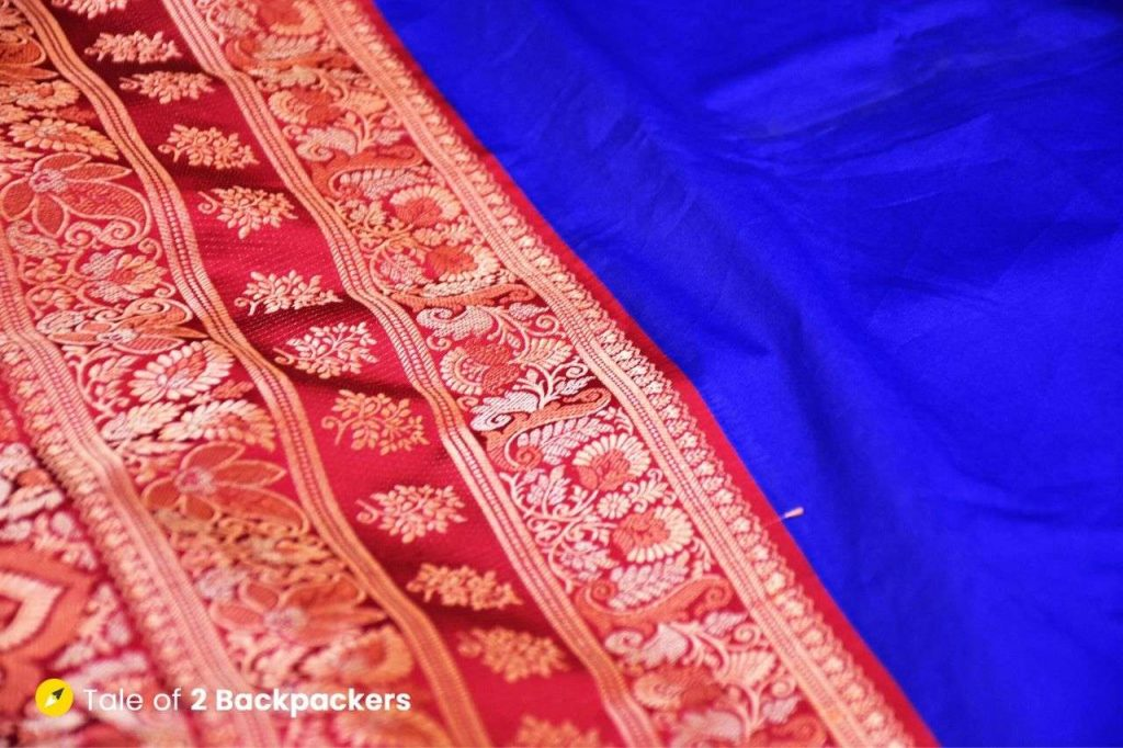A blue and red coloured Banarasi saree displayed in shops