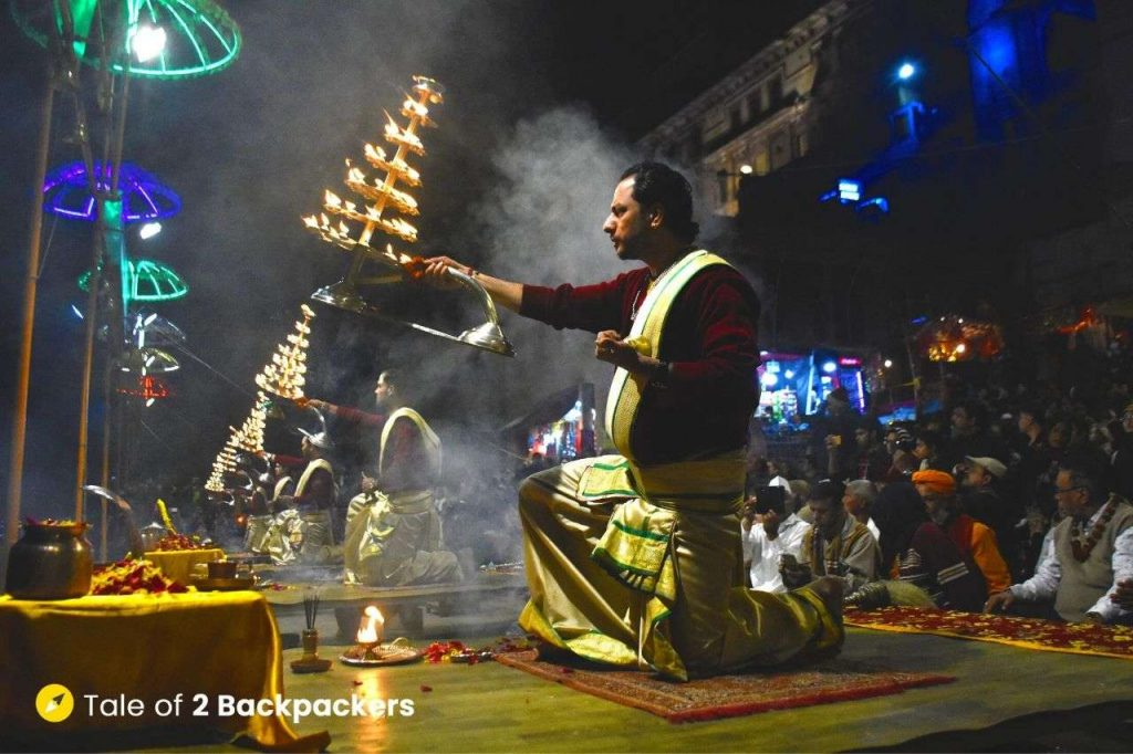 Priests holding tiered lamps during Varanasi Ganga Aarti