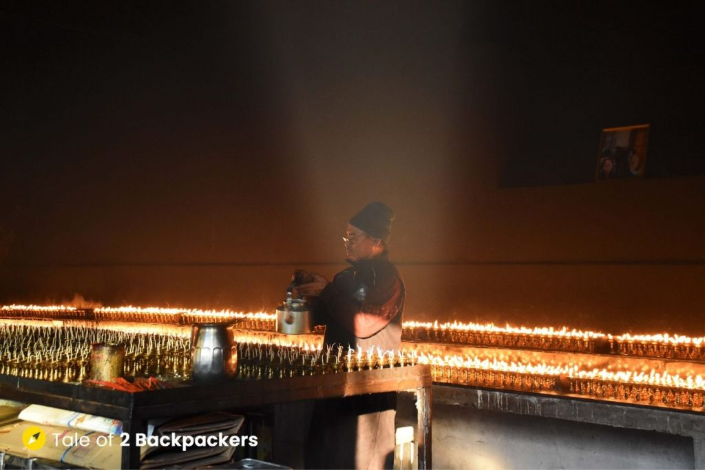 A person lighting butter lamps at Sarnath Tibetan Buddhist Temple