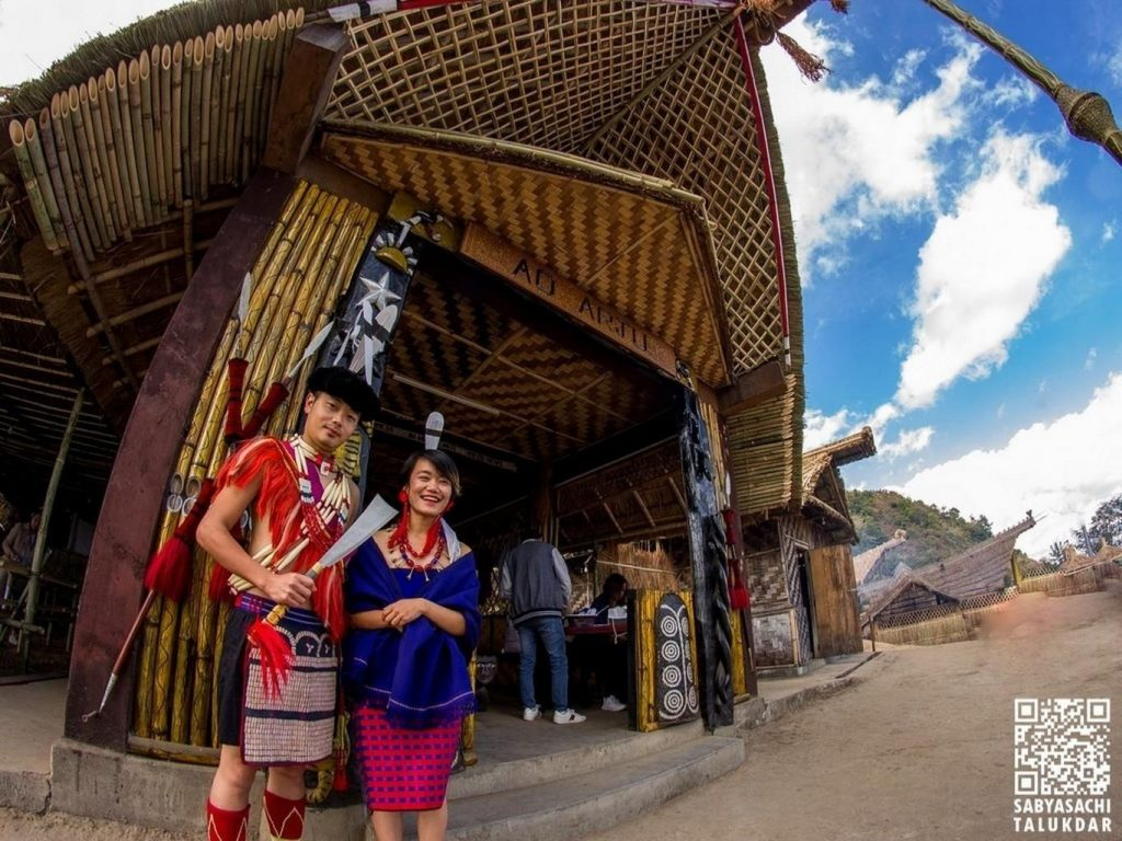 A Naga couple standing in front of a Morung  _ Things to do in Hornbill Festival